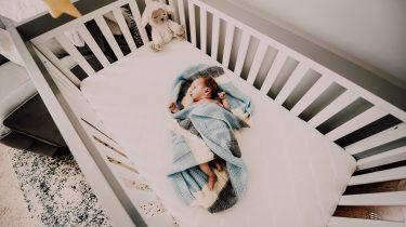 Baby die in zijn eigen bed in zijn eigen kamer ligt te slapen