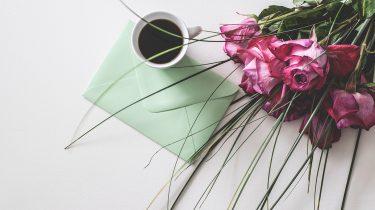 Een moederdagkaart met een kopje koffie en een bos bloemen