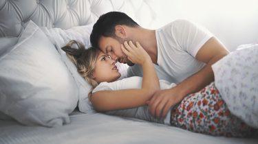 Stelletje in bed dat veel zelfvertrouwen heeft door hun sterrenbeelden