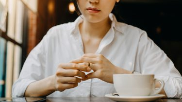 Vrouw die aan tafel zit en met haar trouwring speelt, omdat ze denkt over vreemdgaan