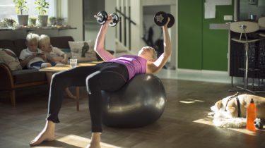 vrouw die thuis fitness oefeningen doet in plaats van in de sportschool
