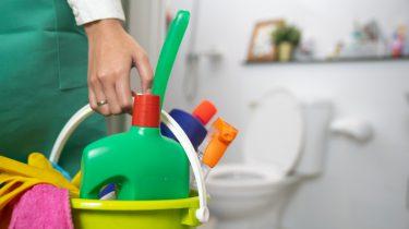 Iemand met een emmertje schoonmaakspullen die de badkamer tegels gaat schoonmaken