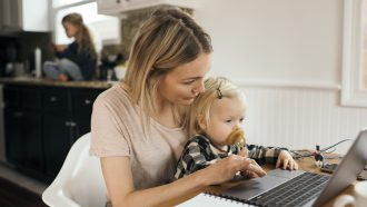 werkende moeder met kind op schoot