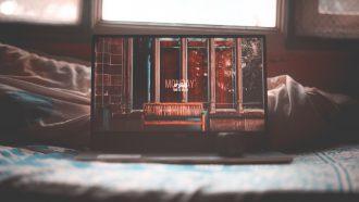 laptop in bed waarop spannende series op netflix worden gekeken