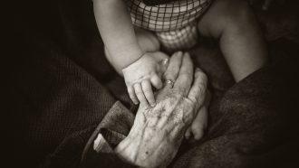 oma houdt handje van baby vast
