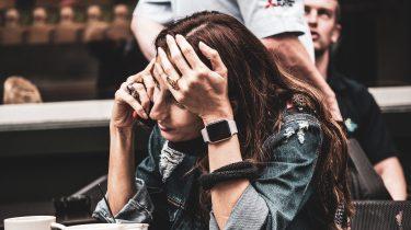 meisje op terras aan de telefoon met stress