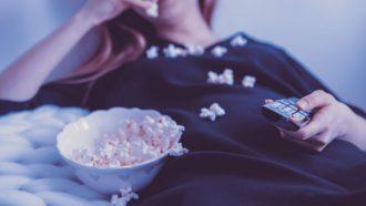 vrouw kijkt series op bank met popcorn