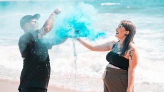Man en vrouw die op het strand een gender reveal party houden