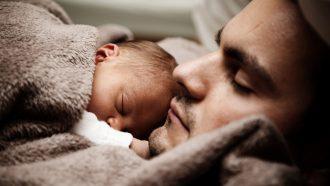Vader en baby hechten in bed