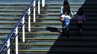 Moeder en dochter op de trap naar school na stress in de ochtend