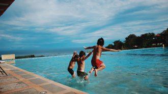 Drie kinderen die in een zwembad springen tijdens een relaxte vakantie