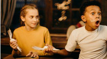 twee kinderen aan tafel tijdens diner