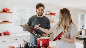 Vrouw die haar partner een van de vragen uit dit lijstje stelt tijdens het koken