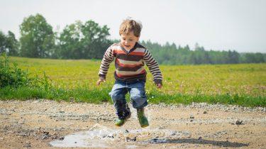 Een jongetje dat in de plassen springt