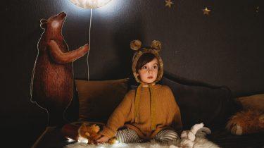 Kind dat rond bedtijd op bed zit in ee berenpyjama, klaar om te slapen
