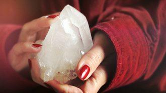 Twee handen die een kristal vasthouden