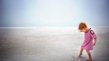 Meisje met rood haar dat op het strand speelt