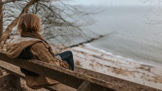 Vrouw zit op een bankje en kijkt uit over zee, ze vraagt zich af of ze overspannen is of een burn-out heeft
