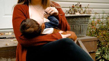 Vrouw die kind borstvoeding geeft