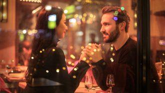 Man en vrouw zitten hand in hand aan tafel