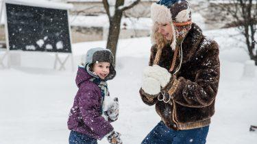 Jongensmoeder en haar zoon die sneeuwballen gooien in de sneeuw
