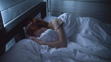 Vrouw die in bed ligt en gek wordt van de jeuk tijdens de zwangerschap