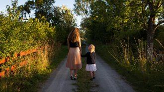 Moeder en dochter lopen hand in hand pratend over school