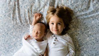 Het eerste kind dat met het tweede kind op bed ligt en trots in de camera kijkt