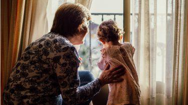opvoeding / oma staat met kleindochter voor het raam