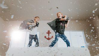 Kinderen alleen thuis die een kussengevecht houden
