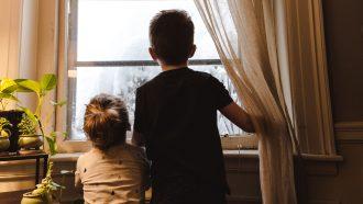Twee kinderen die naar buiten kijken en niet weten welke binnenactiviteiten ze moeten doen
