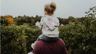 man met kind op zijn schouders