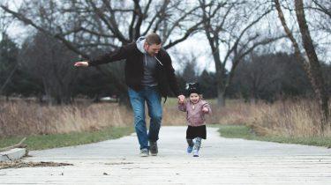 Vader en kind die lekker buiten rennen bij een van de gratis uitjes