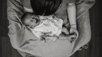 Moeder met huilende baby op haar schoot