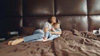 Moeder die met haar zoon op bed ligt en eindelijk weer even contact heeft