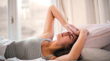 Zwangere vrouw in bed, die zich ellendig voelt in haar eerste trimester