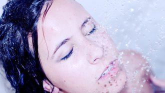Vrouw die onder de douche staat en zich afvraagt hoe vaak ze zich moet douchen