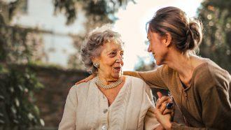 Vrouw die een oudere vrouw helpt die door dementie dingen vergeet