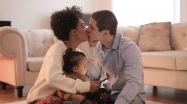 Twee partners die samen een kind opvoeden en elkaar een kus geven