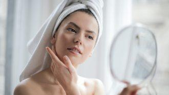 Vrouw die haar puisten bekijkt in de spiegel