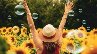 Vrouw die vrolijk is in een veld met zonnebloemen