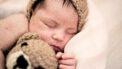 Baby die ligt te slapen met een beer