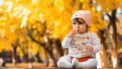 Peuter die buiten in de herfst zit en voedsel eet waarin ze kan stikken