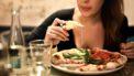 Vrouw die een pizza eet met gesmolten kaas