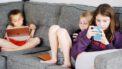 Drie kinderen dieop de bank zitten te gamen